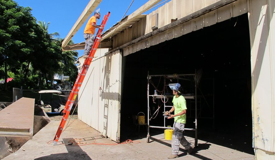 Daniel Kekahuna, left, and Kendal Kanigawa, right, work on a building, Tuesday, Dec. 1, 2015 in Honolulu, that will be converted into a temporary homeless shelter. The 5,000-square-foot shed will accommodate 60 people or 15 families at a time. The shelter, announced Tuesday by Hawaii Gov. David Ige, is intended to connect families with longer-term transitional or permanent housing. People will be allowed to stay up to 90 days.  (AP Photo/Cathy Bussewitz)