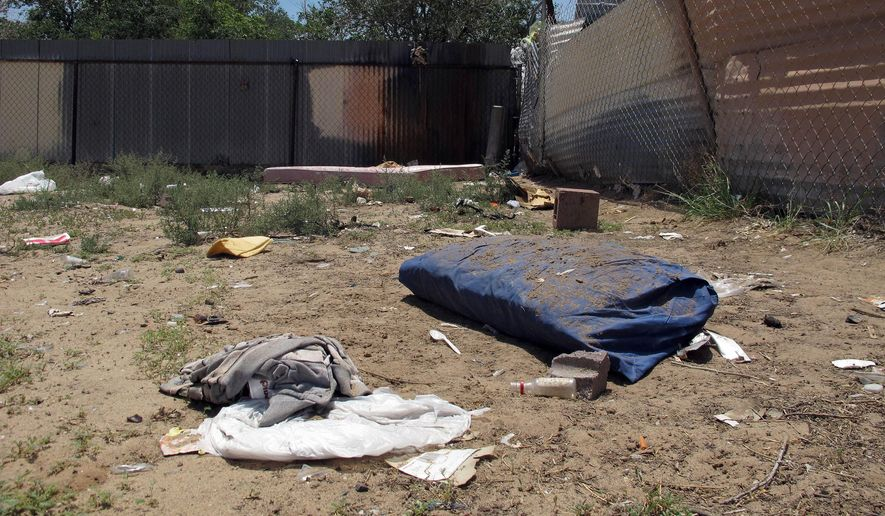 FILE -This July 21, 2014 file photo shows bedding, clothing and broken glass litter a homeless encampment in Albuquerque, N.M. where three teenagers are accused of fatally beating two homeless men. The jury trial for a suspect accused of killing two homeless men who police say were attacked as they slept, and were beaten to death with cinder blocks and other various objects is set to begin Wednesday, Dec. 2, in Albuquerque. (AP Photo/Jeri Clausing,File)