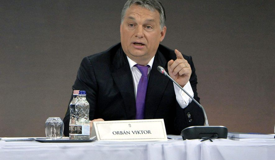 RECROPPED VERSION OF MTI102 -Hungarian Prime Minister Viktor Orban, right, addresses a  session of the Hungarian Diaspora Council, an organization of Hungarians living dispersed all over the world,  in Budapest, Hungary, Wednesday, Dec. 2, 2015. Orban  says he believe a secret pact led by Germany to bring up to 500,000 Syrians from Turkey directly into the European Union to be revealed soon.  (Szilard Koszticsak/MTI via AP)