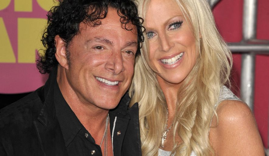 FILE - In this June 6, 2012, file photo, Neal Schon, left, and Michaele Salahi arrive at the CMT Music Awards in Nashville, Tenn. The San Francisco Board of Supervisors on Tuesday, Dec. 1, 2015, approved a $290,000 payout to settle a lawsuit by the guitarist of rock band Journey that claimed the city unfairly jacked up fees to use a city landmark for his lavish wedding. The full board voted unanimously to approve the settlement with Schon.  (Photo by John Shearer/Invision/AP File)