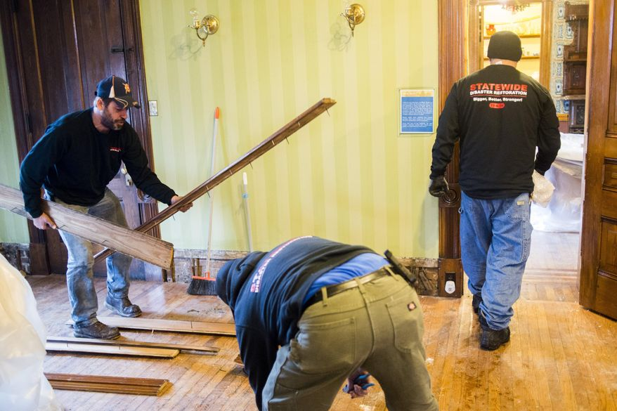 A cleaning crew works to restore the Whaley Historic House Museum on Tuesday, Dec. 1, 2015, near downtown Flint, the day after a fire broke out in the third floor and on the roof, leaving heavy damage throughout the building. Museum president Thomas Henthorn says most of the museum's collections were on the other opposite side of the fire. But he noted that any damage to the house is significant because the house is an artifact.  (Jake May/The Flint Journal-MLive.com via AP) LOCAL TELEVISION OUT; LOCAL INTERNET OUT; MANDATORY CREDIT  (REV-SHARE)  (ONLN OUT; IONLN OUT - MBI)