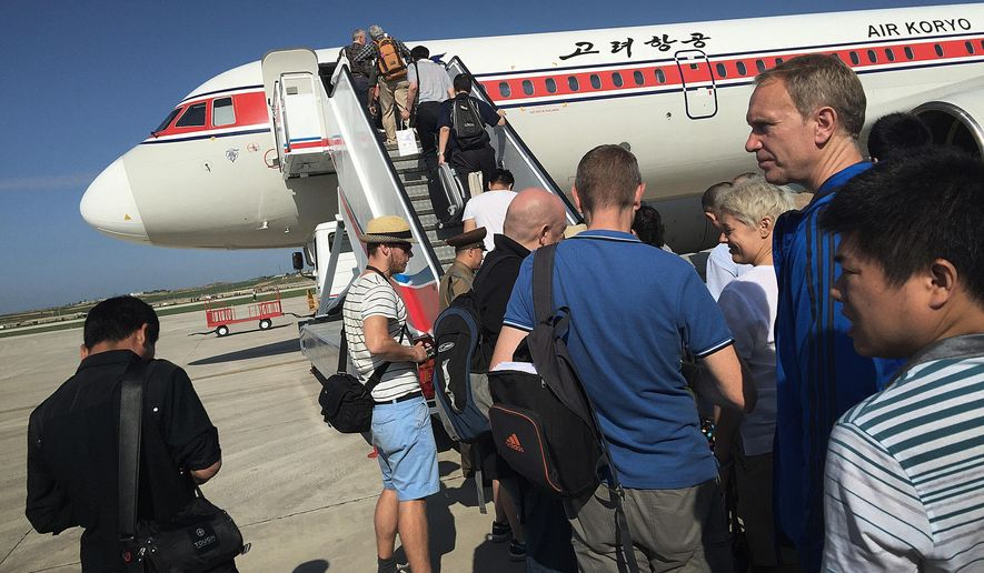 FILE - In this June 27, 2015, file photo, passengers board an Air Koryo plane at the Pyongyang International Airport, in Pyongyang, North Korea. While North Korea is making a strong push to increase the number of tourists who visit the country each year, currently a few thousand come from western countries and more from neighboring China, it is stepping up its enforcement of a broad set of strict but sometimes ambiguously implemented regulations about what foreign visitors can bring with them or what they can do while in the country. (AP Photo/Wong Maye-E, File)