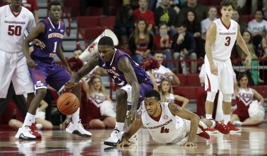 Arkansas' Jabril Durham (4) falls the the floor ahead of Northwestern State's Zeek Woodley (23) while going after the ball during the first half of an NCAA college basketball game, Tuesday, Dec. 1, 2015, in Fayetteville, Ark.  (AP Photo/Samantha Baker)