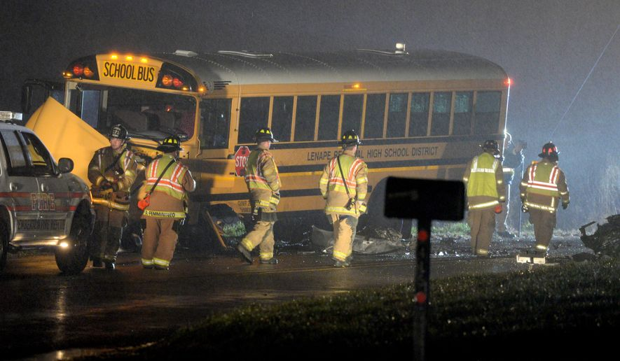 Authorities investigate the scene of an accident involving a school bus and a vehicle on Tuesday, Dec. 1, 2015, in Southampton, N.J. State Police said the school bus and a vehicle collided, leaving at least one person in the car seriously injured. (Tom Gralish/The Philadelphia Inquirer via AP)  PHIX OUT; TV OUT; MAGS OUT; NEWARK OUT; MANDATORY CREDIT