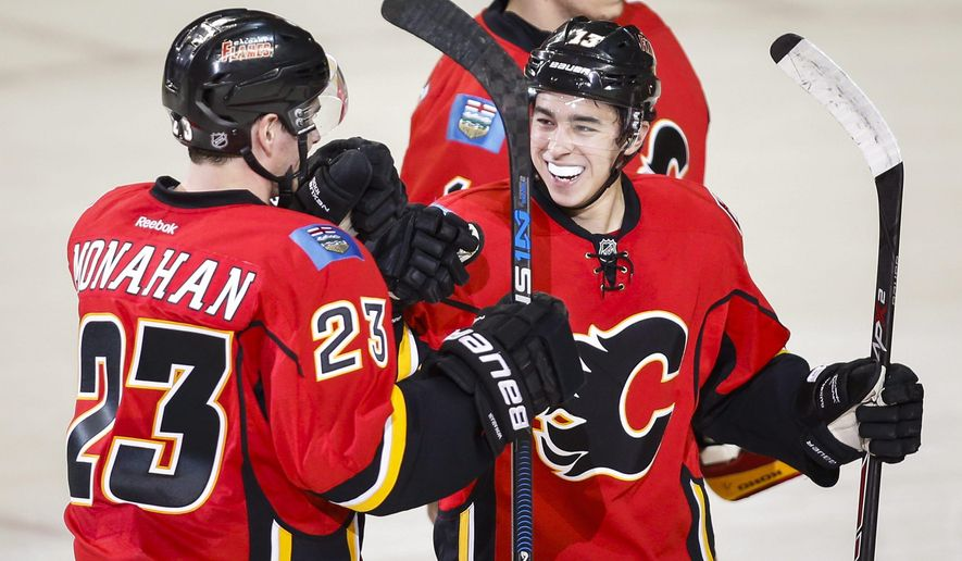 Calgary Flames' Sean Monahan, left, celebrates his game-winning goal against the Dallas Stars with teammate Johnny Gaudreau in an overtime shootout in an NHL hockey game in Calgary, Alberta, Tuesday, Dec. 1, 2015. (Jeff McIntosh/The Canadian Press via AP) MANDATORY CREDIT