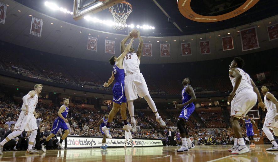 Texas center Cameron Ridley (55) and Texas Arlington forward Jorge Bilbao (45) battle for a rebound during the first half of an NCAA college basketball game, Tuesday, Dec. 1, 2015, in Austin, Texas. (AP Photo/Eric Gay)
