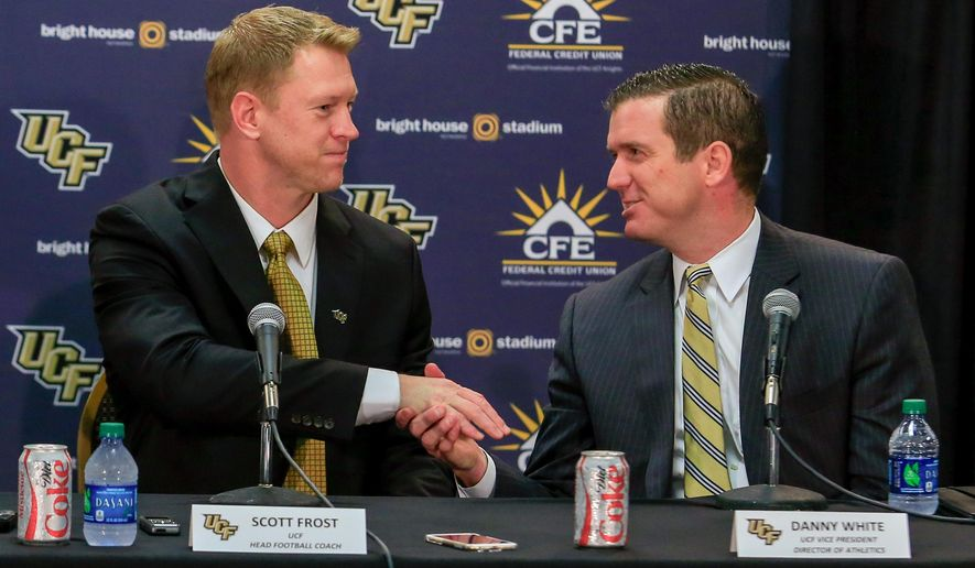 UCF new head NCAA college football coach Scott Frost, left, shakes hands with athletic director Danny White at an introductory news conference in Orlando, Fla., Wednesday, Dec. 2, 2015.  (Joshua C. Cruey/Orlando Sentinel via AP) MAGS OUT; NO SALES; MANDATORY CREDIT
