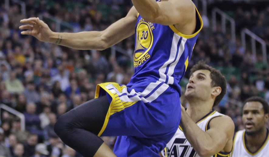 Golden State Warriors guard Stephen Curry (30) goes to the basket as Utah Jazz guard Raul Neto (25) defends in the second quarter of an NBA basketball game Monday, Nov. 30, 2015, in Salt Lake City.  (AP Photo/Rick Bowmer)