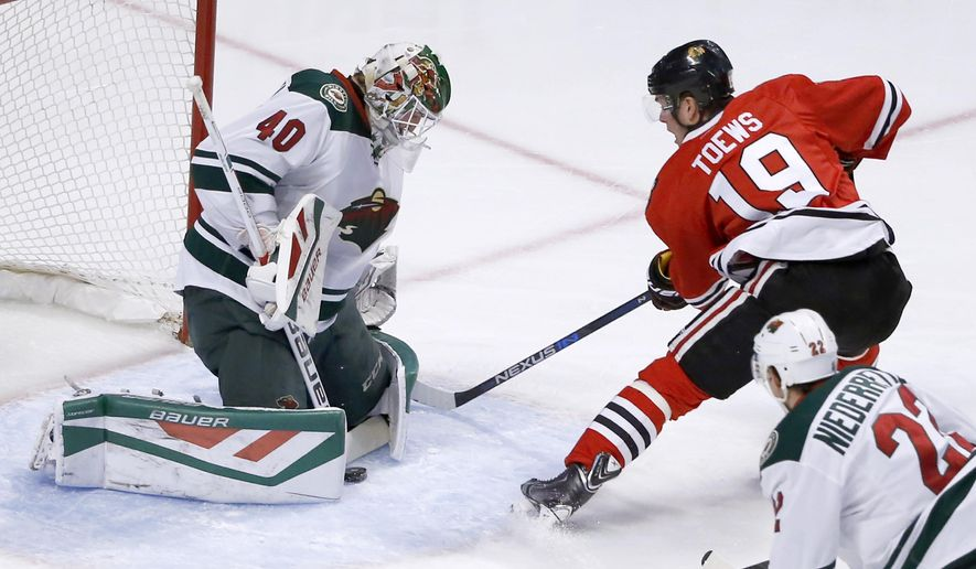 Minnesota Wild goalie Devan Dubnyk makes a save on a point blank shot by Chicago Blackhawks center Jonathan Toews (19) as Nino Niederreiter (22) watches, during the first period of an NHL hockey game Tuesday, Dec. 1, 2015, in Chicago. (AP Photo/Charles Rex Arbogast)