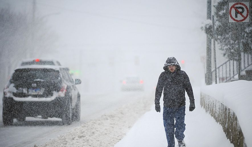Ian Thompson walks home from Sunshine Foods along 14th Street during a winter storm Monday, Nov. 30, 2015, in Sioux Falls, S.D. (Joe Ahlquist/The Argus Leader via AP)