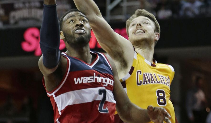 Washington Wizards' John Wall (2) drives to the basket against Cleveland Cavaliers' Matthew Dellavedova (8), from Australia, in the first half of an NBA basketball game Tuesday, Dec. 1, 2015, in Cleveland. (AP Photo/Tony Dejak)