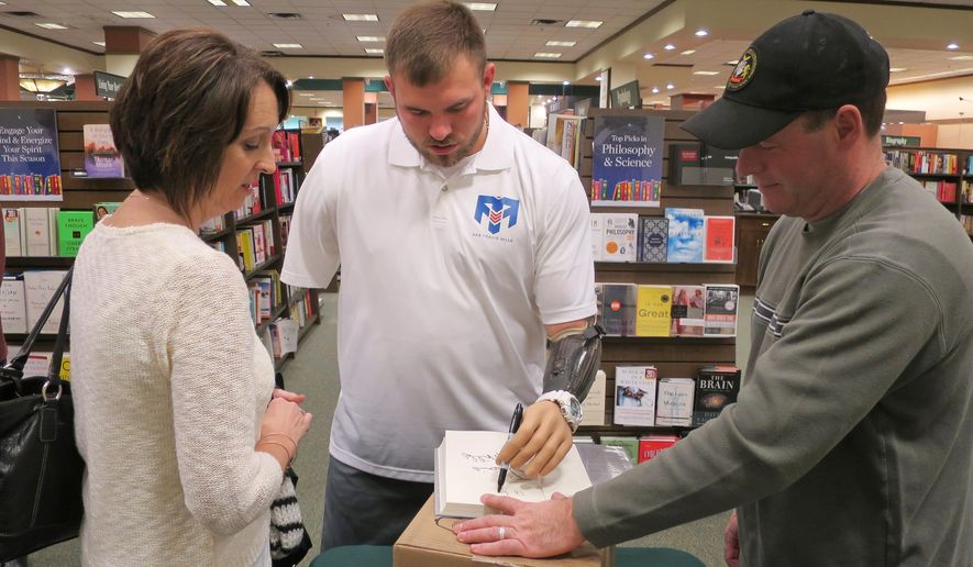 """Retired Army Staff Sgt. Travis Mills, center, signs a book for Lori Jones, left, of Unity, Maine, whose husband became ill and died after a deployment to Iraq, at an event promoting Mills' book, """"Tough As They Come,"""" on Tuesday, Dec. 1, 2015, in Augusta, Maine.  Mills, who lives in Manchester, Maine, lost all four limbs as a result of an IED blast in 2012 in Afghanistan. (AP Photo/David Sharp)"""