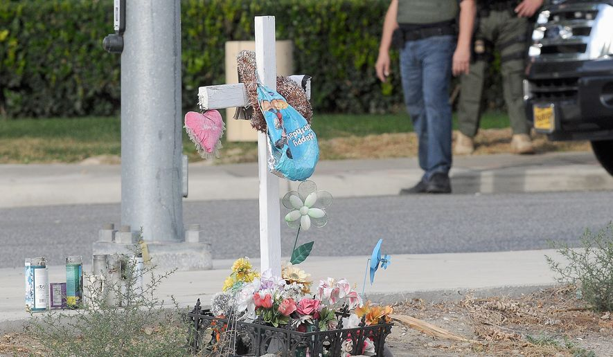 A small memorial is set up across from the Inland Regional Center in San Bernardino, California, a day after a bloodbath from gunfire left many people dead and injured. (The Victor Valley Daily Press via Associated Press)