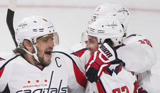 Washington Capitals' T.J. Oshie (77) celebrates with teammates Alex Ovechkin (8) and Nicklas Backstrom (19) after scoring against the Montreal Canadiens during the third period of an NHL hockey game Thursday, Dec. 3, 2015, in Montreal. (Graham Hughes/The Canadian Press via AP)