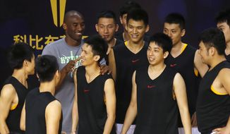 NBA star Kobe Bryant chats with Chinese basketball players during a meeting with fans in China's southern city of Shenzhen, Sunday Aug. 4, 2013. Kobe Bryant visited Shenzhen as part of his China tour. (AP Photo/Kin Cheung)