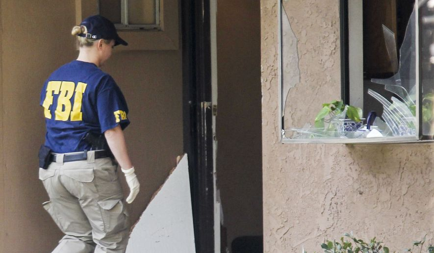 A FBI agent searches outside a home in connection to the shootings in San Bernardino, Thursday, Dec. 3, 2015, in Redlands, Calif.. A heavily armed man and woman opened fire Wednesday on a holiday banquet for his co-workers, killing multiple people and seriously wounding others in a precision assault, authorities said. Hours later, they died in a shootout with police. (AP Photo/Ringo H.W. Chiu)