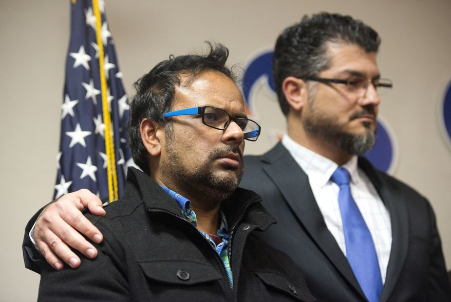 Farhan Khan, left, brother-in-law of one of the suspects involved in a shooting in San Bernardino, Calif., is held by Hussam Ayloush, executive director of Council on American-Islamic Relations, during a news conference at the Greater Los Angeles Area office of the Council on American-Islamic Relations, in Anaheim, Calif. Multiple attackers opened fire on a banquet at a social services center for the disabled in San Bernardino on Wednesday, killing multiple people and sending police on a manhunt for suspects. (Matt Masin/The Orange County Register via AP) MAGS OUT; LOS ANGELES TIMES OUT; MANDATORY CREDIT