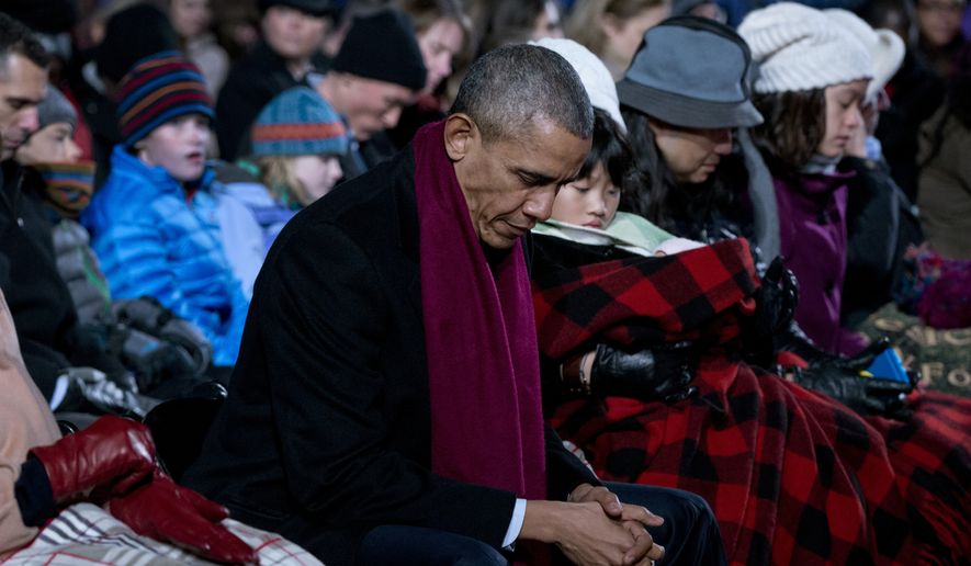 President Barack Obama bows his head in prayer during the National Christmas Tree Lighting ceremony at the Ellipse in Washington, Thursday, Dec. 3, 2015. (AP Photo/Carolyn Kaster)