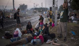 Syrian refugees wait near the border railway station of Idomeni, northern Greece, in order to be allowed by the Macedonian police to cross the border from Greece to Macedonia, Tuesday, Aug. 25, 2015. Greece has been overwhelmed this year by record numbers of migrants who have been arriving on a number of Greek islands. (AP Photo/Santi Palacios, File)