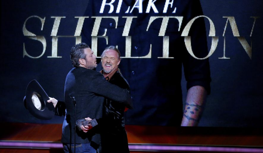 Blake Shelton, left, tries to give a kiss to Trace Adkins after receiving his award at the 2015 Artist of the Year Show at Schermerhorn Symphony Center Wednesday, Dec. 2, 2015, in Nashville, Tenn. (Photo by Donn Jones/Invision/AP)