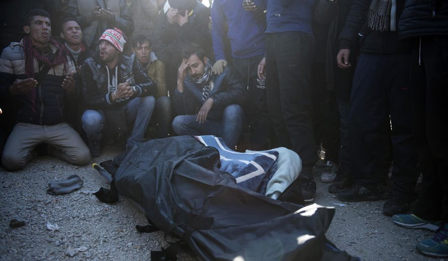 Stranded migrants sit next a covered body of a man believed to be from Morocco, at the Greek-Macedonian border, near the northern Greek village of Idomeni, Thursday, Dec. 3, 2015. The man was electrocuted after touching high-power overhead railway cables when he climbed on top of a train carriage. (AP Photo/Giannis Papanikos)