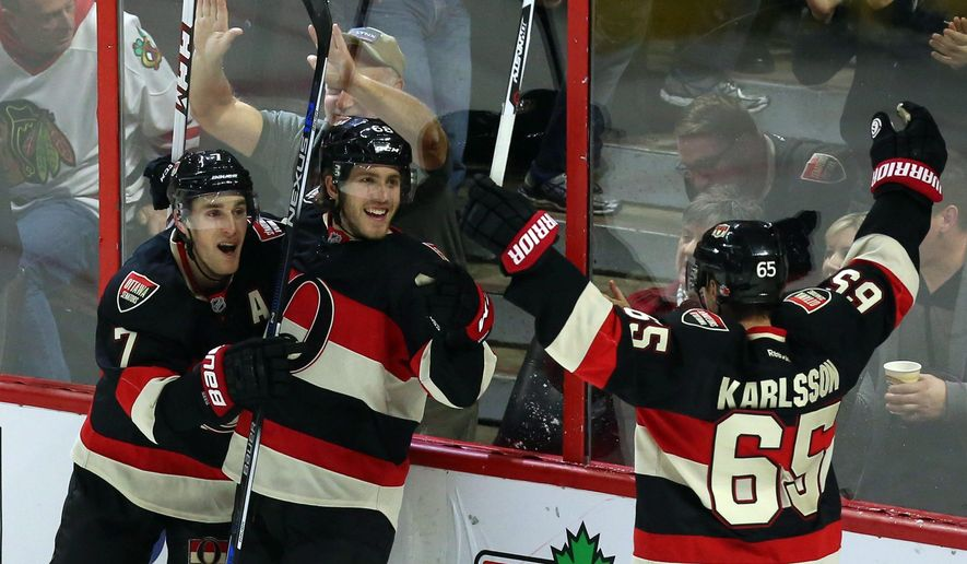 Ottawa Senators' Mike Hoffman (68) celebrates his game winning overtime goal against the Chicago Blackhawks with teammates Erik Karlsson (65) and Kyle Turris (7) during an NHL hockey game in Ottawa, Ontario, Thursday, Dec. 3, 2015. (Fred Chartrand/The Canadian Press via AP) MANDATORY CREDIT