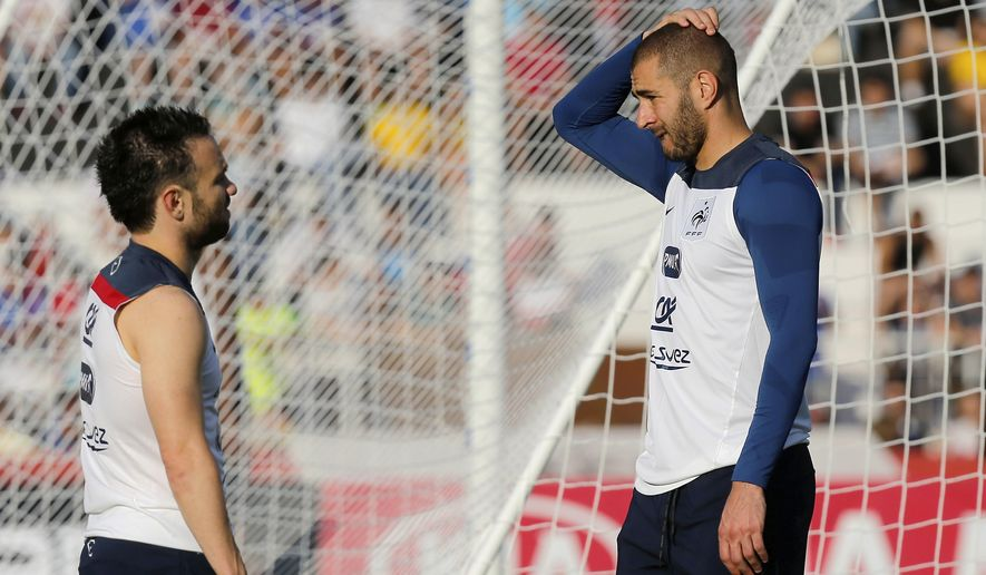 FILE - In this June 10, 2014 file photo, France's Mathieu Valbuena, left, and Karim Benzema, right, chat during a training session of the french national soccer team, at the Santa Cruz Stadium in Ribeirao Preto, Brazil. Speaking publicly for the first time since becoming embroiled in a blackmail scandal, Karim Benzema said Wednesday Dec.2, 2015 he wants to play again for France and win the 2016 European Championship with teammate Mathieu Valbuena. (AP Photo/David Vincent, File)