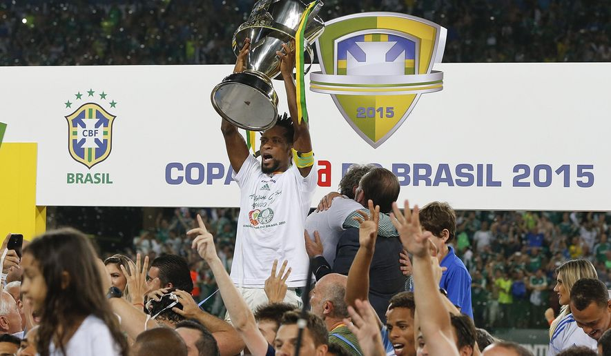 Palmeiras' Ze Roberto holds up the trophy as he celebrates with teammates after defeating Santos at the end of the Copa do Brasil final soccer match in Sao Paulo, Brazil, Thursday, Dec. 3, 2015. Palmeiras won in a penalty shootout after a 2-2 draw on aggregate.(AP Photo/Andre Penner)