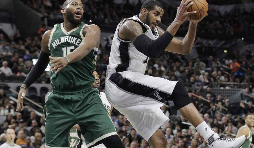 San Antonio Spurs forward LaMarcus Aldridge (12) pulls down a rebound in front of Milwaukee Bucks center Greg Monroe (15) during the first half of an NBA basketball game, Wednesday, Dec. 2, 2015, in San Antonio. (AP Photo/Eric Gay)