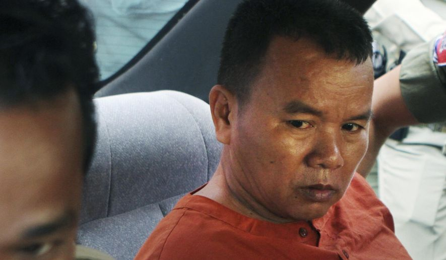 Yem Chrin, left, an unlicensed medical practitioner, sits in a car as escorting by prison guards after a verdict announcing of the Battambang provincial court in Battambang province, northwest of Phnom Penh, Cambodia, Thursday, Dec. 3, 2015. The Cambodian court sentenced Yem Chrin to 25 years in prison Thursday after finding him responsible for infecting more than 100 villagers with HIV, the virus that causes AIDS, by reusing unsanitized syringes. At least 10 of the infected people have died. (AP Photo/Mai Vireak)