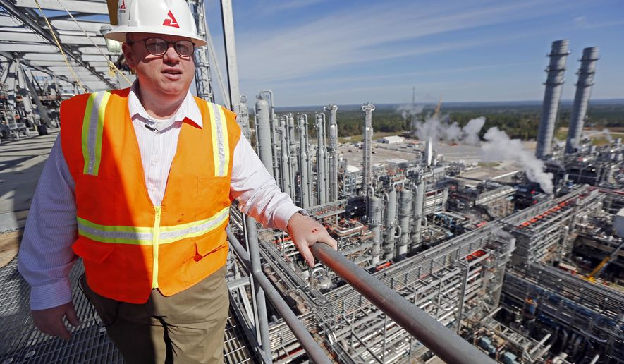 In this Nov. 16, 2015 photo, Mississippi Power spokesman Lee Youngblood, talks about the carbon capture power plant in DeKalb, Miss., while standing on the top floor of the gasifier unit, some 218 feet above the pine forests and pastures. The construction costs for the plant have grown to $6.4 billion and it has been repeatedly delayed, but Southern Company, owners of Mississippi Power, stand by the plant as a model for burning coal while emitting less carbon dioxide and hope to market its key technology. (AP Photo/Rogelio V. Solis)