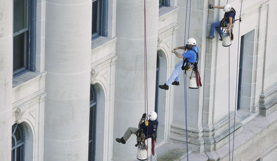 FILE - In this Sept. 8, 2014 file photo, from left, Logan Cook, Steve Naggatz and Sarah Sinusas, of Wiss, Janney and Elstner, a Chicago engineering firm, rappel down the side of the state Capitol as they inspect the building for upcoming repairs, in Oklahoma City. A panel overseeing a $120 million renovation of the state Capitol are expected to be presented with a final projection for how much more the undertaking will cost. (AP Photo/Sue Ogrocki, File)