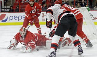 Carolina Hurricanes goalie Eddie Lack (31) blocks a shot on goal by New Jersey Devils' Lee Stempniak during the first period of an NHL hockey game in Raleigh, N.C., Thursday, Dec. 3, 2015. (AP Photo/Gerry Broome)