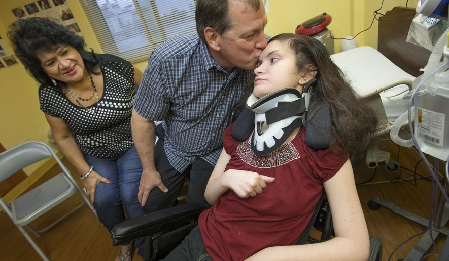 ADVANCE FOR SUNDAY, DEC. 6 AND THEREAFTER - Aaron Hrachovina leans over to kiss his daughter Sarah, 24,  while sitting with his wife Teresa in Sarah's room at The Meridian in Galveston Tuesday, Nov. 17, 2015.  An auto accident with a drunk driver in 2010 left Sarah fighting for her life.   (Stuart Villanueva/The Galveston County Daily News via AP) MANDATORY CREDIT, NO SALES, TV OUT