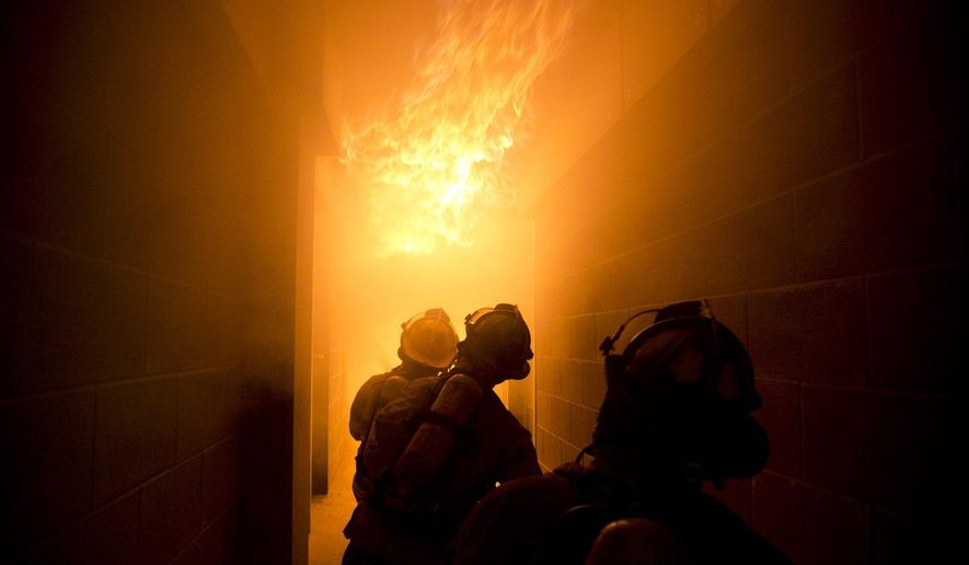 Firefighters in training crouch in a hallway fighting a test fire on Thursday, Nov. 19, 2015.The Fort Worth Fire Department's old burn building and tower has been out of service for the past 15 years, but a new high-tech burn tower piped with natural gas is providing training opportunities from rookies to veteran firefighters. (Joyce Marshall/Star-Telegram via AP)  MAGS OUT; (FORT WORTH WEEKLY, 360 WEST); INTERNET OUT; MANDATORY CREDIT