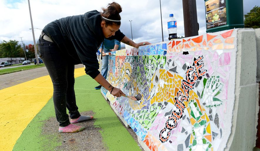 ADVANCE FOR WEEKEND EDITIONS, DEC. 5-6 - In this photo taken Oct. 9, 2015, Marissa Nelson-Russell applies sealant to one of the mosaics as part of the Project RestART, a partnership between Peckham and the MSU Residential College in the Arts and Humanities and College of Engineering in Lansing, Mich. Project RestART began with ideas back in 2012 and morphed into artistic mosaics on concrete barricades now placed on the Racer Trust site in Saginaw. (Dave Wasinger/Lansing State Journal via AP)  NO SALES; MANDATORY CREDIT