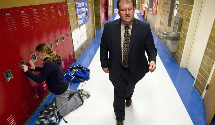 ADVANCE FOR USE MONDAY, DEC. 7 - In this photo taken Nov. 18, 2015, Jeff Sampson, superintendent for both LeRoy-Ostrander and Southland, Minn. school districts,  walks down a school hallway in Adams, Minn. Sampson says that  his staff will be trained in run, hide, fight procedures this January. The goal is to prepare staff and students to respond to a number of situations, including an active shooter inside the building. (Andrew Link/The Rochester Post-Bulletin via AP) MANDATORY CREDIT