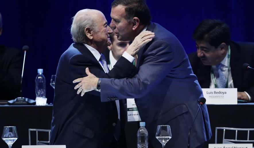 FILE - In this March 4, 2015 file photo FIFA President Sepp Blatter, left, congratulates Juan Angel Napout after the Paraguayan was confirmed as president of CONMEBOL during a general congress of the South American football confederation, in Asuncion, Paraguay. On Thursday, Dec. 3, 2015 Switzerland's justice ministry has identified FIFA vice presidents Juan Angel Napout and Alfredo Hawit as the two officials arrested today on suspicion of bribery.  (AP Photo/Jorge Saenz)