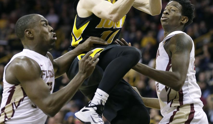 Iowa guard Mike Gesell, center, drives to the basket between Florida State's Montay Brandon, left, and Jarquez Smith, right, during the second half of an NCAA college basketball game, Wednesday, Dec. 2, 2015, in Iowa City, Iowa. Iowa won 78-75 in overtime. (AP Photo/Charlie Neibergall)