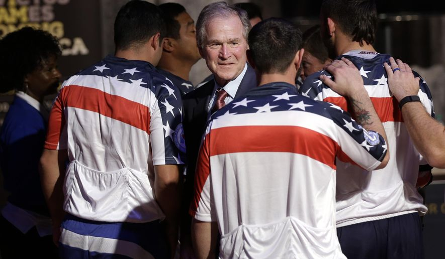 Former President George W. Bush gets into huddle with wounded veterans after a demonstration of sitting volleyball at the Intrepid Sea, Air and Space Museum in New York, Thursday, Dec. 3, 2015. Sitting volleyball will be one of the adaptive sports to be played during the Invictus Games, a competition between wounded veterans from around the globe. Bush will serve as the honorary chair of the games and the George W. Bush Institute will co-chair a policy symposium on veteran's health. (AP Photo/Seth Wenig)