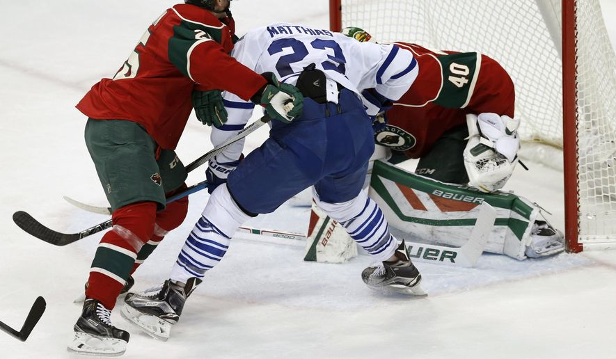 Toronto Maple Leafs' Shawn Matthias, center, looks for the puck as Minnesota Wild goalie Devan Dubnyk, right, and Wild's Jonas Brodin, of Sweden, protect the net during the first period of an NHL hockey game, Thursday, Dec. 3, 2015, in St. Paul, Minn. (AP Photo/Jim Mone)