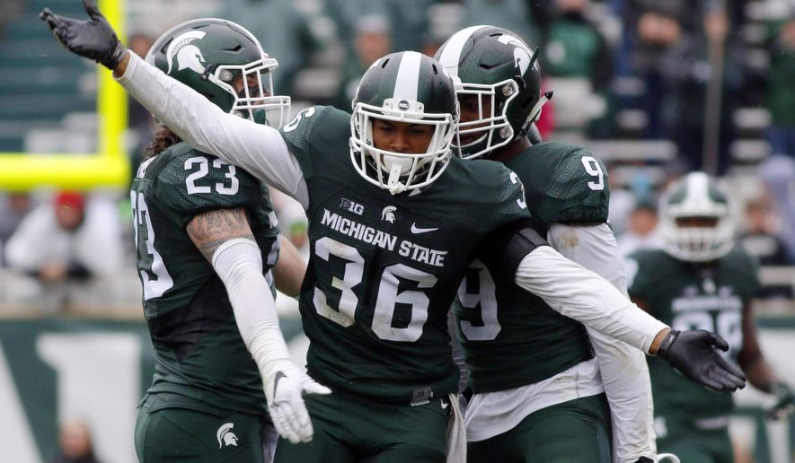 FILE - In this Oct. 3, 2015, file photo,Michigan State's Arjen Colquhoun (36), Chris Frey (23) and Montae Nicholson celebrate a play during the fourth quarter of an NCAA college football game against Purdue in East Lansing, Mich. About a month ago, Michigan State's secondary cost the Spartans a shot at an undefeated season, and a Big Ten title seemed unlikely unless things improved quickly. Now, that maligned group of defensive backs is gaining confidence, and preparing to take the field for the conference title game. (AP Photo/Al Goldis, File)