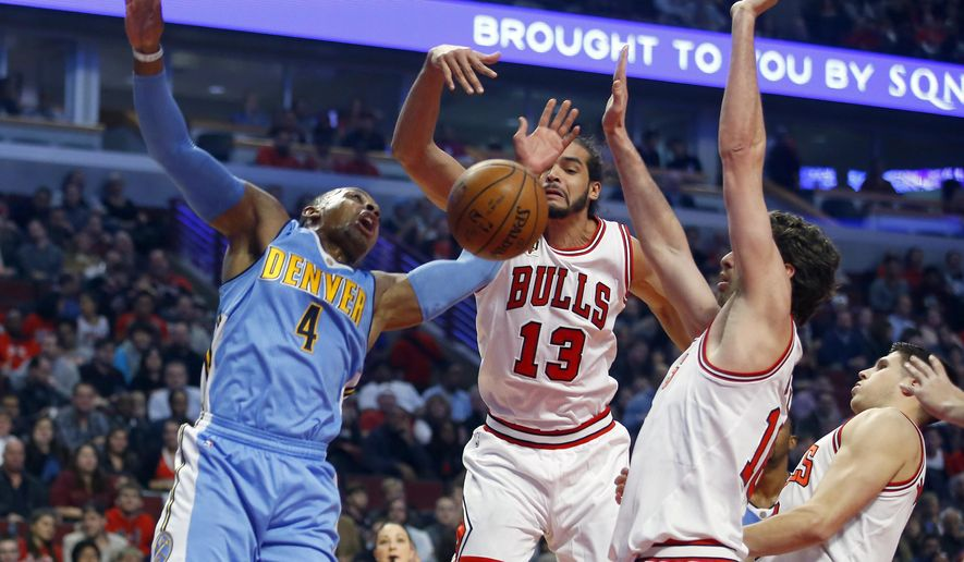 Chicago Bulls center Joakim Noah (13) strips the ball from Denver Nuggets guard Randy Foye (4) during the first half of an NBA basketball game in Chicago, Wednesday, Dec. 2, 2015. (AP Photo/Jeff Haynes)
