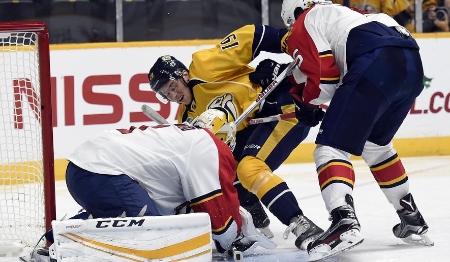 Florida Panthers goalie Roberto Luongo (1) covers up the puck after a shot by Nashville Predators center Calle Jarnkrok (19), of Sweden, as Panthers defenseman Aaron Ekblad (5) defends in second period of an NHL hockey game Thursday, Dec. 3, 2015, in Nashville, Tenn.  (AP Photo/Mark Zaleski)