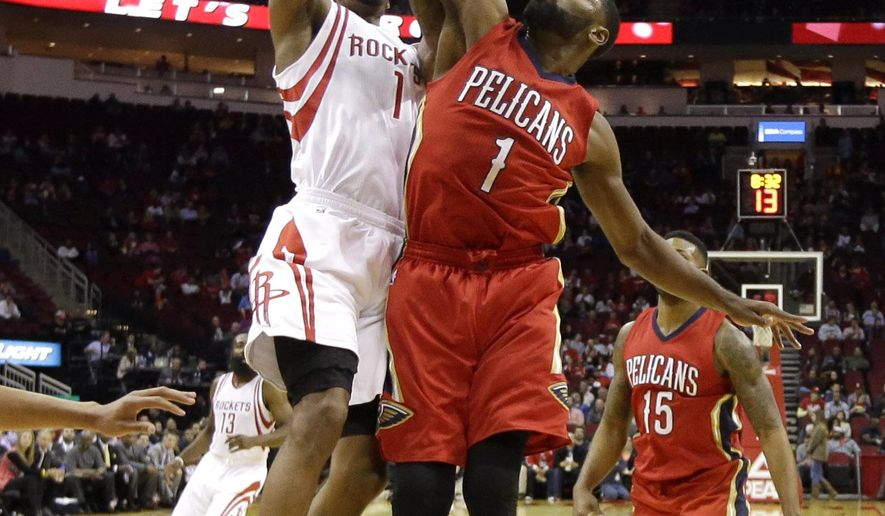 Houston Rockets' Trevor Ariza, left, has his shot blocked by New Orleans Pelicans' Tyreke Evans, during the first quarter of an NBA basketball game, Wednesday, Dec. 2, 2015, in Houston. (AP Photo/David J. Phillip)