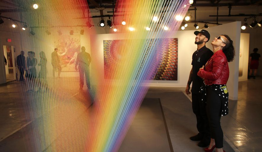 Musician Alicia Keys, right, and her husband hip hop recording artist and producer Swizz Beatz, left, look at an installation by artist Gabriel Dawe at Casa Bacardi's art fair and Untameable House Party, Thursday, Dec. 3, 2015, in Miami. The no-commission art fair was curated by Beatz, and both Keys and Beatz will perform during the Untameable House Party. Both events were timed to coincide with Art Basel Miami Beach. (AP Photo/Lynne Sladky)
