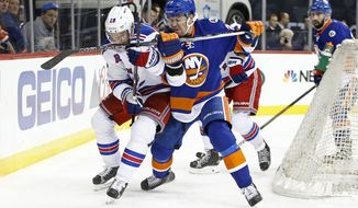 New York Islanders defenseman Marek Zidlicky (28), of the Czech Republic, defends New York Rangers center Dominic Moore (28) behind the Islanders net in the first period of an NHL hockey game at the Barclays Center in New York, Wednesday, Dec. 2, 2015. (AP Photo/Kathy Willens)