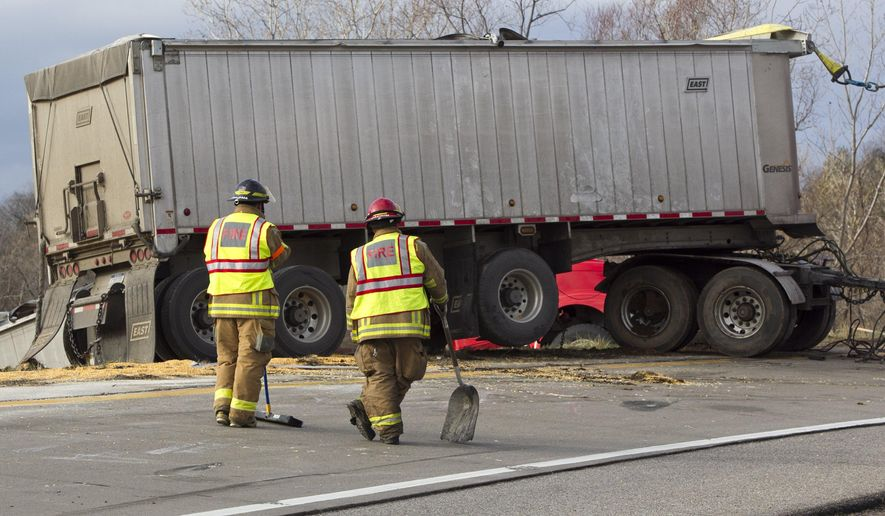 Members of the Walker Fire Department respond to the scene after a semi truck rolled over at the southbound U.S. 131 entrance to eastbound I-96, Thursday, Dec. 3, 2015. The truck spilled corn. (Cory Morse/The Grand Rapids Press/MLive.com via AP)