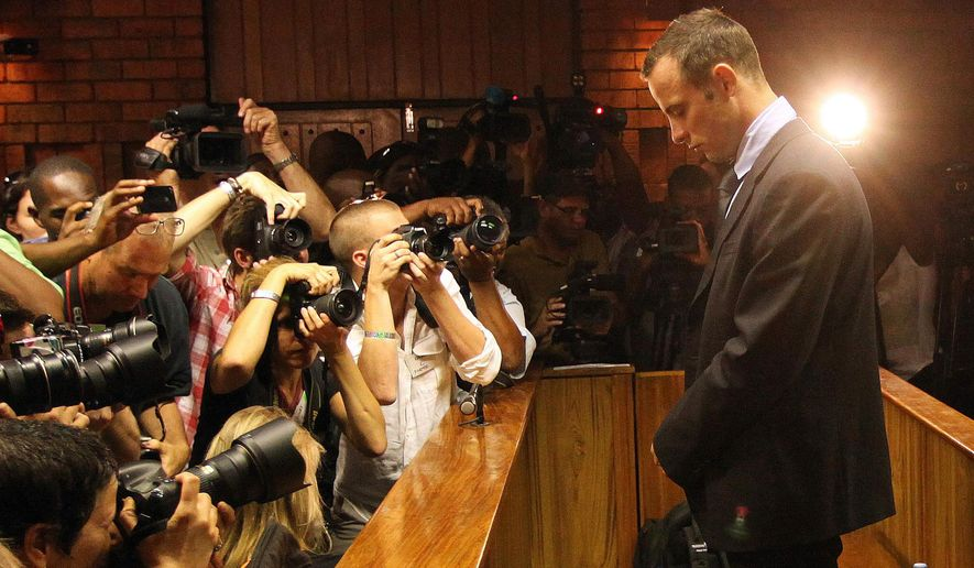 FILE - In this Friday, Feb 22, 2013 file photo photographers take photos of Olympic athlete Oscar Pistorius as he appears at a bail hearing for the shooting death of his girlfriend Reeva Steenkamp, in Pretoria, South Africa.   The South African court of appeal Thursday Dec. 3 2015 has convicted Pistorius of murder, overturning his manslaughter conviction.  (AP Photo/Themba Hadebe, File)