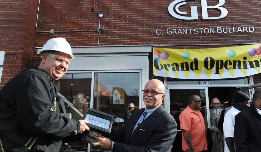 "Detroit Power Systems Field Supervisor Vic Selewski, left, and Wayne County Executive Warren Evans pose for a ceremonial photo with an LED light to be installed above C. Grantston Bullard Design Studio following a press conference Wednesday, Dec. 2, 2015,  inside the shop announcing the ""Historic Avenue of Fashion Business District Lighting Project"" on Livernois Avenue in Detroit. The Greater Wayne County Economic Development Corp. awarded the project a $106,000 grant to pay for installation of 160 LED lights around businesses, in alleys, and in parking lots in the area.   (Brandy Baker/Detroit News via AP)  DETROIT FREE PRESS OUT; HUFFINGTON POST OUT; MANDATORY CREDIT"